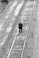 man walking on railroad tracks in the countryside