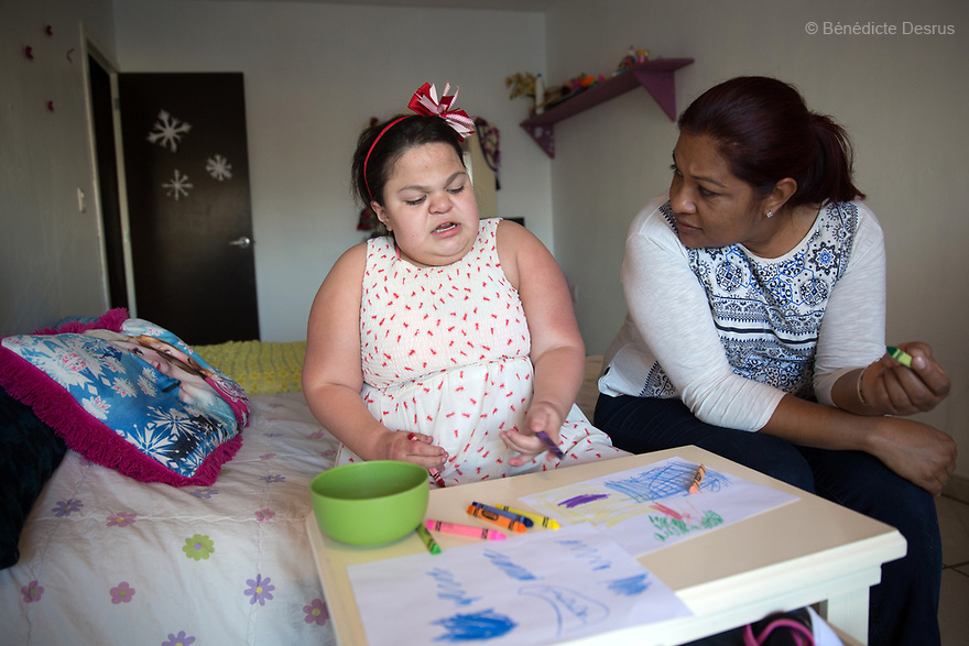 "Ana Ximena Navarro (L) is pictured drawing with her aunt Gabriela Rios Ballesteros (R), at her home in Guadalajara, Mexico on February 22, 2017. Ximena was diagnosed as an infant with Hurler syndrome. Hurler syndrome is the most severe form of mucopolysaccharidosis type 1 (MPS1), a rare lysosomal storage disease, characterized by skeletal abnormalities, cognitive impairment, heart disease, respiratory problems, enlarged liver and spleen, characteristic facies and reduced life expectancy. Ximena was being given enzyme replacement therapy (ERT) when she was 19 months old, and she was suddenly able to eat and sleep. She is now 12, and has normal hormonal development for her age, although some mental delay, according to her father. ""Without the treatment, she would have died from all the complications — untreated, children have a very bad quality of life and typically die before they are seven"", her father says. Photo credit: Bénédicte Desrus"
