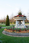 Beautiful flowerbeds surround a planter with winged lions on a  sunny spring day in Regent's Park, London, England