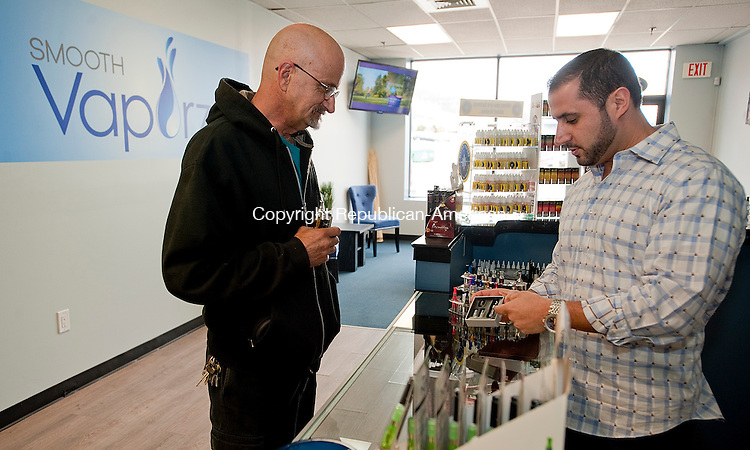 WATERBURY, CT-030314JS12--Nick Ricciardi, of Smooth Vapors on Watertown Avenue in Waterbury, right, talks with customer Ray Coer, Jr., of Waterbury about the new mini pro tank II vapor tank for use in his e-cigarette. Coer used to smoke a minimum of three packs of cigarettes a day until he switched over to the vapor method. <br /> Jim Shannon Republican-American