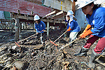 Maryglen Roa (left), Jeanette Ayo and Maryann Lloveras clean up debris in Tacloban, a city in the Philippines province of Leyte that was hit hard by Typhoon Haiyan in November 2013. The storm was known locally as Yolanda. They are participants in a United Nations funded cash for work program.