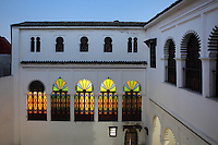 Facades of the internal courtyard with whitewashed walls, arched colonnades and stained glass, in a typical Tetouan riad, a traditional muslim house built around a courtyard, built in Moorish style with strong Andalusian influences, next to the Great Mosque or Jamaa el Kebir in the Medina or old town of Tetouan, on the slopes of Jbel Dersa in the Rif mountains of Northern Morocco. Tetouan was of particular importance in the Islamic period from the 8th century, when it served as the main point of contact between Morocco and Andalusia. After the Reconquest, the town was rebuilt by Andalusian refugees who had been expelled by the Spanish. The medina of Tetouan dates to the 16th century and was declared a UNESCO World Heritage Site in 1997. Picture by Manuel Cohen