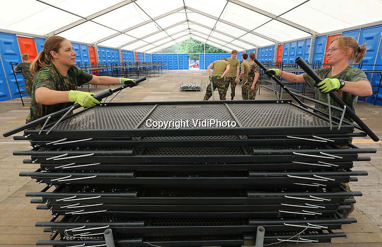 Foto: VidiPhoto<br /> <br /> NIJMEGEN - Op het militaire kamp Heumensoord in Nijmegen zijn maandag de voorbereidingen voor de Nijmeegse Vierdaagse in volle gang. Voor het eerst wordt de inrichting van de tientallen verblijven voor de ruim 5000 buitenlandse militairen door Defensiepersoneel zelf gedaan. Om te  besparen op de kosten worden geen uitzendkrachten meer ingehuurd. Alleen het bouwen van de enorme tenten gebeurt nog door burgers. Inclusief bewaking en verzorging verblijven in de Vierdaagseweek (16, 17, 18 en 19 juli) zo'n 6000 personen van 33 nationaliteiten op deze tijdelijke kazerne.