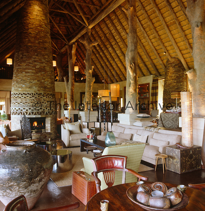 The main living area has two sitting rooms either side of a double-volume stone-clad fireplace with a row of Leadwood tree trunk pillars supporting the roof