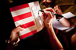 GOP Presidential candidate Rep. Michele Bachmann signs a copy of the US Constitution at a town hall event in Muscatine, Iowa, July 24, 2011.