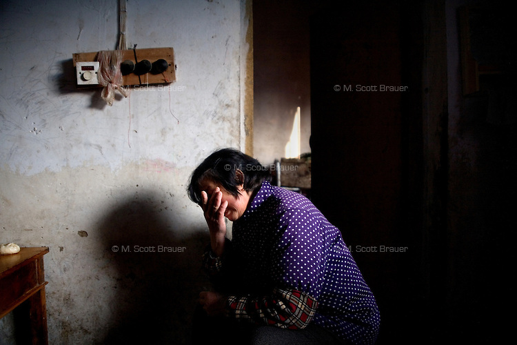 Huo Yang Xia cries as she describes the life of her orphaned grandson Fan Wen Jie, 11, who lives with her in Fanzhuan Village, Jiangsu Province, China. The boy's father died in a car crash in 2005, and his mother remarried in 2006, abandoning the boy, though she still periodically sends money to help the family.  The boy's grandparents are frequently ill, and the meager income from farming cannot support him.   ..At the time of the picture, China's Amity Foundation charity, was investigating the family's situation in preparation to raise money to financially support these children and other orphans in similar situations.  With Amity's support, each orphan, aged 6-12, would receive approximately 1,400 RMB annually (about 200 USD) to pay for the cost of living. Amity works to keep children out of the institutional orphanages in China, preferring to provide monetary assistance that can help maintain a family environment for the orphans it helps.