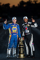 Nov 13, 2016; Pomona, CA, USA; NHRA funny car driver Ron Capps (left) and top fuel driver Antron Brown pose for a portrait with the world championship trophies after clinching their classes championships during the Auto Club Finals at Auto Club Raceway at Pomona. Mandatory Credit: Mark J. Rebilas-USA TODAY Sports