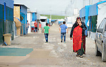A woman walks in a camp for internally displaced families in Ankawa, near Erbil, Iraq. Residents of the camp, mostly Christians, were displaced from Mosul, Qaraqosh and other communities in Iraq when ISIS swept through the area in 2014.