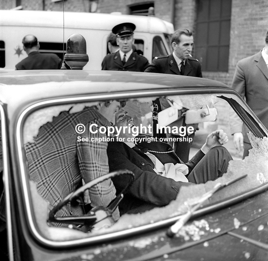 RUC Constable Eric Aiken lies injured in the passenger seat of a patrol car which came under gun attack by the Provisional IRA when it halted at traffic lights at Durham Street-Divis Street. The driver was able to make it back to Springfield Road police station where an ambulance has just arrived. Later police released a statement which said that Constable Aiken was &quot;comfortable&quot;. The incident happened August 1971. 19710800083<br />