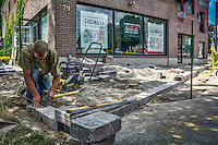 Installing decorative blocks for a wall that will be then anchor for a wrought iron fence outside Cucinova in Uptown Westerville.