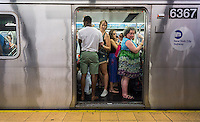 Passengers crowd into a subway train in New York on Sunday, July 12, 2015. Weekend service for travelers consists of less trains and service disruptions due to maintenance. (© Richard B. Levine)