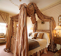 A double bed with an opulent fabric canopy in a traditoinal guest bedroom.