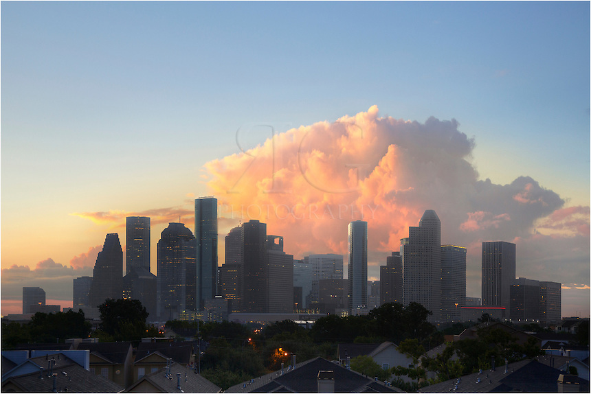 A large thunderstorm looms over downtown Houston. While it looks menacing, the actual storm was many miles away and the rains never reached the city. This photograph was taken in the early morning as the sun's light was striking the billowing clouds high in the atmosphere.