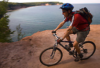 A mountain biker rides through a cliff overlook of North Bay on Grand Island National Recreation Area in Munising Michigan.