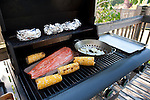 Barbecue in backyard with salmon onions, bakers and corn