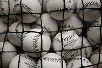 Detail photo of baseballs piled in a batting practice bin with Major League Baseball and Rawlings logo prominent. Seattle Mariners at Texas Rangers. Photographed at Rangers Ballpark In Arlington in Arlington, Texas on Sunday, April 11, 2010. Photograph &copy; 2010 Darren Carroll.
