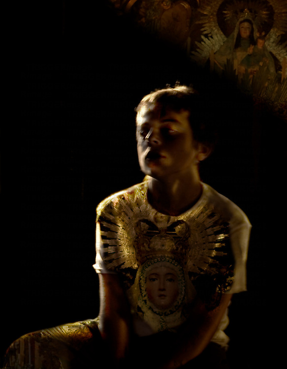 A young boy sitting in sunlight with religious iconography on a t-shirt