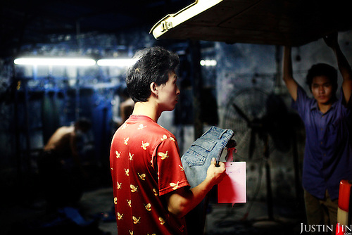 """A manager checks a jeans sample in Mr Huang's factory in Zhongshan city, China.  .This picture is part of a photo and text story on blue jeans production in China by Justin Jin. .China, the """"factory of the world"""", is now also the major producer for blue jeans. To meet production demand, thousands of workers sweat through the night scrubbing, spraying and tearing trousers to create their rugged look. .At dawn, workers bundle the garment off to another factory for packaging and shipping around the world..The workers are among the 200 million migrant labourers criss-crossing China.looking for a better life, at the same time building their country into a.mighty industrial power."""