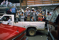 Farm families crowd in a truck on the way home from the market. Streets are clogged when the market closes for the day in this small mountain town. Families load into the back of a truck for transportation home. Chaos dominates a normally quiet Huastec village when the narrow streets fill on Sunday morning with people buying and selling locally grown coffee and sugarcane, copal incense and huge corn tamales..South of Ciudad Valles the Pan American Highway passes through Huasteca Indian country. At one time the Huastec population was once.estimated to be one million, but today they number about.150,000.