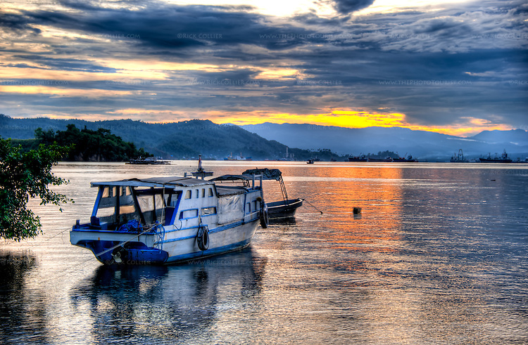 The setting sun illuminates the rainy season cloud cover and reflects in the waters of the Lembeh Strait (view west from the Lembeh Resort toward Bitung and North Sulawesi, Indonesia).  (HDR image)