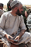 Commander Ghosadeen, who leads about two dozen men of a village militia, holds a pistol as he talks to U.S. and Canadian soldiers outside Zhormashor, in Dand district, near Kandahar, Afghanistan. With U.S. and Afghan forces unable to reach many rural areas, they are relying increasingly on village militias to arm and protect themselves against the Taliban. June 27, 2010. DREW BROWN/STARS AND STRIPES