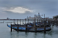 Gondolas moored in front of St Mark's Square or the Piazza San Marco, and behind, the Punta della Dogana with the Basilica di Santa Maria della Salute, designed by Baldassare Longhena in Baroque style, built 1631-87, Venice, Italy. On the left is the Chiesa del Santissimo Redentore or Church of the Most Holy Redeemer, designed by Andrea Palladio in Renaissance style and consecrated 1592, on Giudecca island. The city of Venice is an archipelago of 117 small islands separated by canals and linked by bridges, in the Venetian Lagoon. The historical centre of Venice is listed as a UNESCO World Heritage Site. Picture by Manuel Cohen
