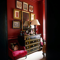 The red color palette is broken up by the antique Russian chest of drawers and the display of drawings and prints hanging on the wall