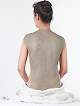 Woman with bentonite clay body wrap mask on her back