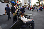 A street musician plays his sax while a woman reads a book in Mexico city's main avenue of Benito Juarez, November 14, 2012. Street daily life in Mexico City..Photo by Heriberto Rodriguez