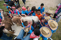 NWA Democrat-Gazette/ANTHONY REYES &bull; @NWATONYR<br /> George elementary students pet miniture horses Thursday, April 23, 2015 at the annual Stick Horse Rodeo at the Parsons Stadium in Springdale. The students participated in a number of activities with a rodeo theme including roping, stick horse riding, music and riding a bucking barrel.