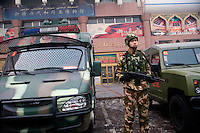 An armed policeman stands watch in the Uighur section of Urumqi, Xinjiang, China. The city is divided between Han and Uighur ethnicities, and violent clashes erupted between the groups in 2009.