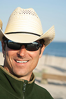 handsome man in a cowboy hat and sunglasses smiling