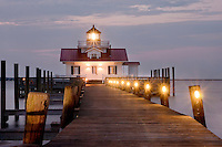 A boardwalk lined with lights leading to Roanoke Marshes Lighthouse at twilight.