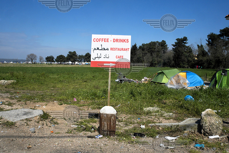 A sign in English and Arabic indicates a cafe and restaurant near a makeshift refugee camp at Idomeni. Around 14,000 people were stranded in the camp which the authorities have since closed and distributed the occupants among several official camps around the country.