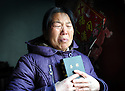 WANG, 53, WEEPS AS SHE RECEIVES HER FIRST BIBLE AT A RURAL CHURCH IN HENAN PROVINCE, CHINA...JAN 2010....FILENAME:CHINA206(2)....CLARE KENDALL..07971 477316