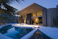Dramatic view of ultra modern architecture house across blue pool at night