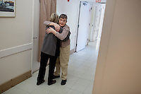 Regina Davidson (left) hugs her sister Marily Davidson, 70, a resident at Malone Park at the Fernald Developmental Center.  Marilyn is high functioning and can speak.  She has lived in the Malone Park residences at the Fernald Center for 9 years, after living elsewhere on the campus before.  She likes to spend time looking and smiling in her mirror.