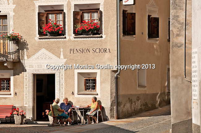 Hotel with local women sitting out front in the small town of Promotogno, a Swiss town in the Bregaglia Valley. The decorations on the house are patterns scratched out of the still wet wall, decorative artwork called sgraffiti, traditionally done in two colors and originating in Italy, brought to the Engadin region of Switzerland in the 16th century and is still used today