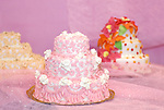 Colorful fancy multi-layered wedding cakes on pink background