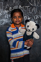 Muskan, 5, poses for a portrait with a soft toy in the Guria Non-Formal Education center in the middle of the Shivdaspur red light district, Varanasi, Uttar Pradesh, India on 20 November 2013. Guria uses the soft toys as a form of therapy for the children of the women in prostitution and also use it as signals of the children's emotional wellbeing.