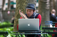 A man works on his Apple Macbook Pro in Bryant Park in New York City