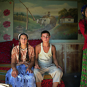 A Roma couple sit in front of a Transylvanian rural scene mural painted on the wall of their home, in the old part of the Sintesti Roma camp. .