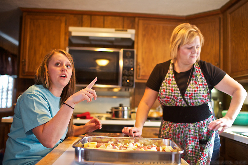 "Lynett and Karly, wife and daughter of Lance Frederick, owner of the custom harvesting company, preparing lunch in the family trailer. They live and travel in this trailer for about 7 months of the year...Life of custom harvesters: custom harvesting or custom combining is the business of harvesting of crops for others. Custom harvesters usually own their own combines and work for the same farms every harvest season. Custom harvesting relieves farmers from having to invest capital in expensive equipment while at the same time maximizing the machinery's use. .Harvesters travel North to South through the US, living in trailers, following the season, usually hiring overseas seasonal workers in need of improving their harvesting experience on very large combines (harvesting machines)...A 4-weeks road trip across the USA, from New York to San Francisco, on the steps of Jack Kerouac's famous book ""On the Road"".  Focusing on nomadic America: people that live on the move across the US, out of ideology or for work reasons."