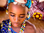 Dressed in her brightest, finest clothing, made-up, and wearing the hallmark silver coin jewelry of the Fulani of Niger, 9-year old Dicko readies herself to walk the five or so miles from her village in southwestern Niger to the town of Torodi. In Torodi, she will sell the fruit of the karey tree that she worked so hard to gather the past week.