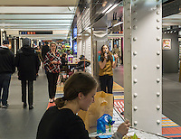 "A woman takes a lunch break as Hannah Florence, performing in Cirque du Soleil's Broadway musical ""Paramour"", sings songs from the musical at a lunchtime performance in Turnstyle, a shopping and foodie arcade in the subway in New York Tuesday, November, 29, 2016. ""Paramour"" is at the Lyric Theatre and is about the golden age of Hollywood. (© Richard B. Levine)"