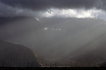 Windmill farm in the desert, stormy weather with  San Bernadino Mountains in background near Palm Springs, California USA