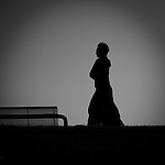 A middle aged woman walking alone outdoors by a bench