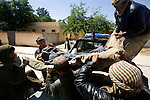 Afghan border policemen help unload the bodies of two policemen who were killed by a roadside bomb at the morgue at Mirwais Hospital in Kandahar, Afghanistan, April 23, 2009. The day before, Ahmad Shei, 25, and Hamidullah, 22, were in an unarmored truck carrying material to a checkpoint in Zabul Province when their vehicle was hit by a roadside bomb. Four other border policemen were injured and taken to Kandahar Air Field to receive medical treatment. The two dead were to the morgue at Mirwais Hosptal before being transported to their home provinces in the North for burial. Despite worsening security, development continues at Mirwais Hosptial, where the International Committe of the Red Cross conducts training and assists the local staff. Mirwais is the main public hosptial serving five southern provinces. As security has deteriorated in the South, many international NGO's have pulled their staff from the area or shut down the regional office, stunting development in a region where it is badly needed.