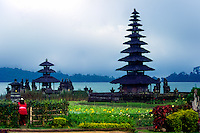 Bali, Tabanan, Bratan. The Ulun Danu temple is beautifully situated at the banks of Lake Bratan. A woman brings offerings.