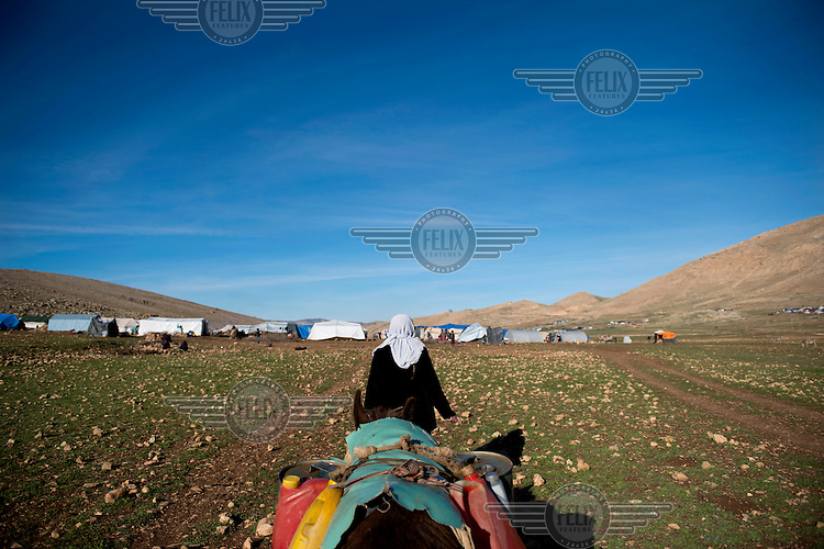 A Yazidi woman hauls water containers on the back of a donkey toward a Yazidi refugee camp in the Sinjar mountains. <br /> Thousands of Yazidis fled to the mountains when Islamic State (IS) fighters attacked towns and villages around Sinjar in August 2014. Since then Yazidi refugees have been living in precarious conditions with no electricity or running water and children haven't been attending school. Support from the international community has been insufficient and people are dying of hunger and disease. Until December 2014 the mountains were surrounded by IS. Now the southern part of the mountains is still under IS control.